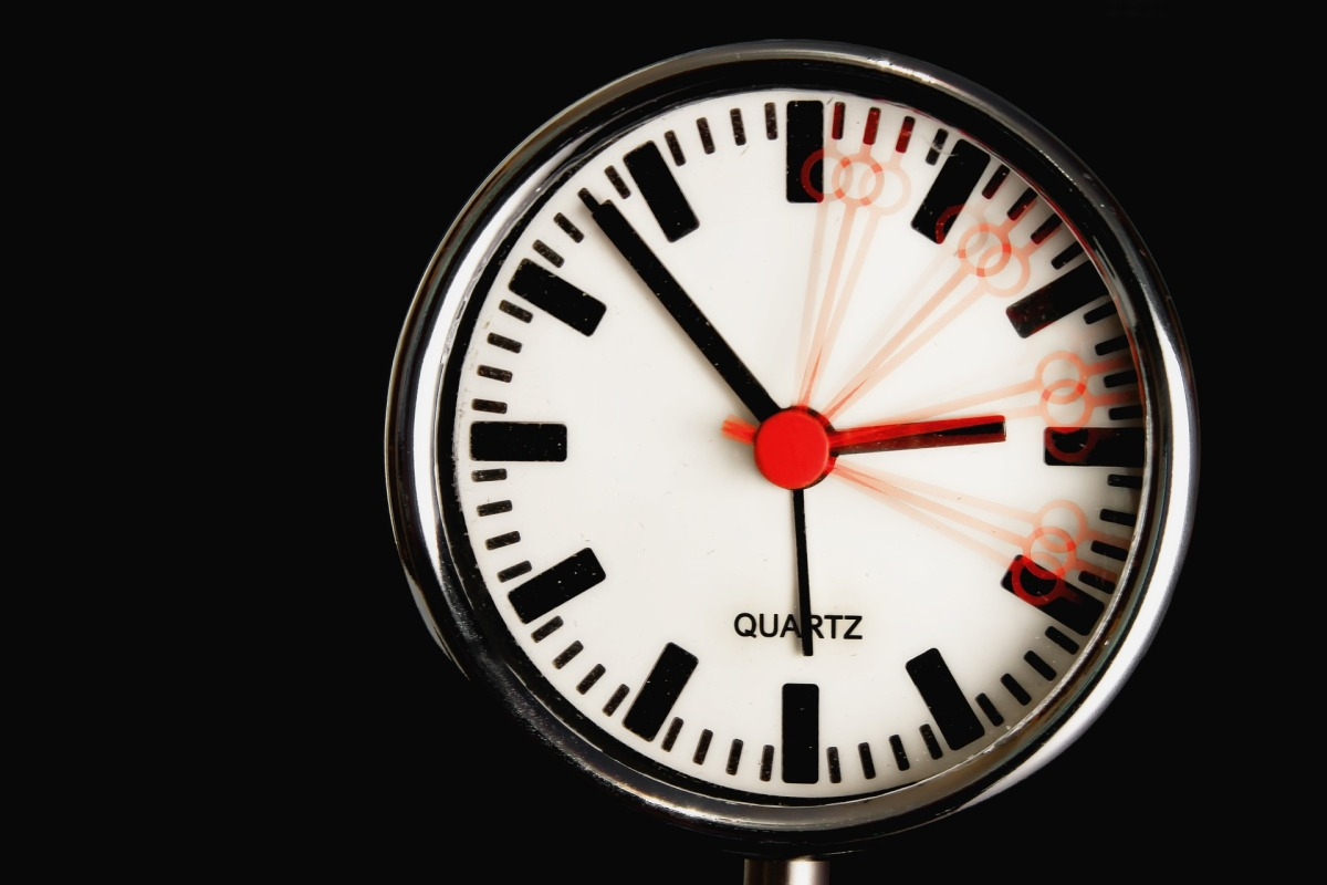 A white clock on a black background. The hour labels are only marked with lines, not numbers. The clock has three black arms showing minute, hour, and seconds, but a fourth red arm is blurred as if to show rapid, wild motion around from the 12:00 to the 4:00 places.