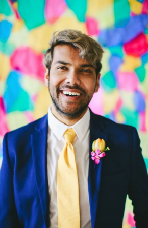 A photo of Tau Zaman smiling, wearing a blue suit with a yellow tie and a boutonnière of yellow and pink flowers. They are standing in front of a vibrant background of yellow, pink, teal, and blue abstract shapes.