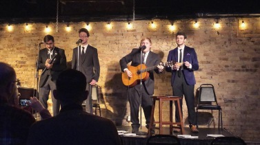 Four people dressed in suits stand on a stage, singing. One plays a classical guitar. The stage is in front of a brick wall and is lit by large string lights.