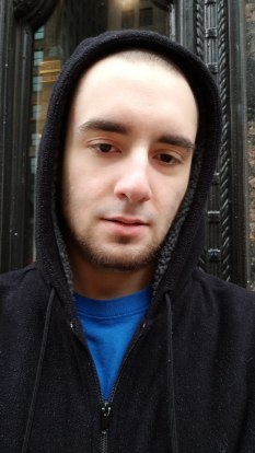 Jack Peterson, a white man with slight facial hair wearing a black hoodie with the hood up over a blue tee shirt.