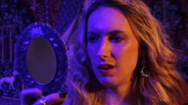 Natalie Wynn, a woman with long blond hair wearing earrings and a tiara, looking into a mirror, lit by deep purple from her right